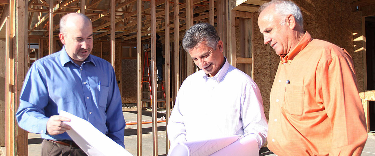 The SJVHomes owners looking at plans in front of a framed home