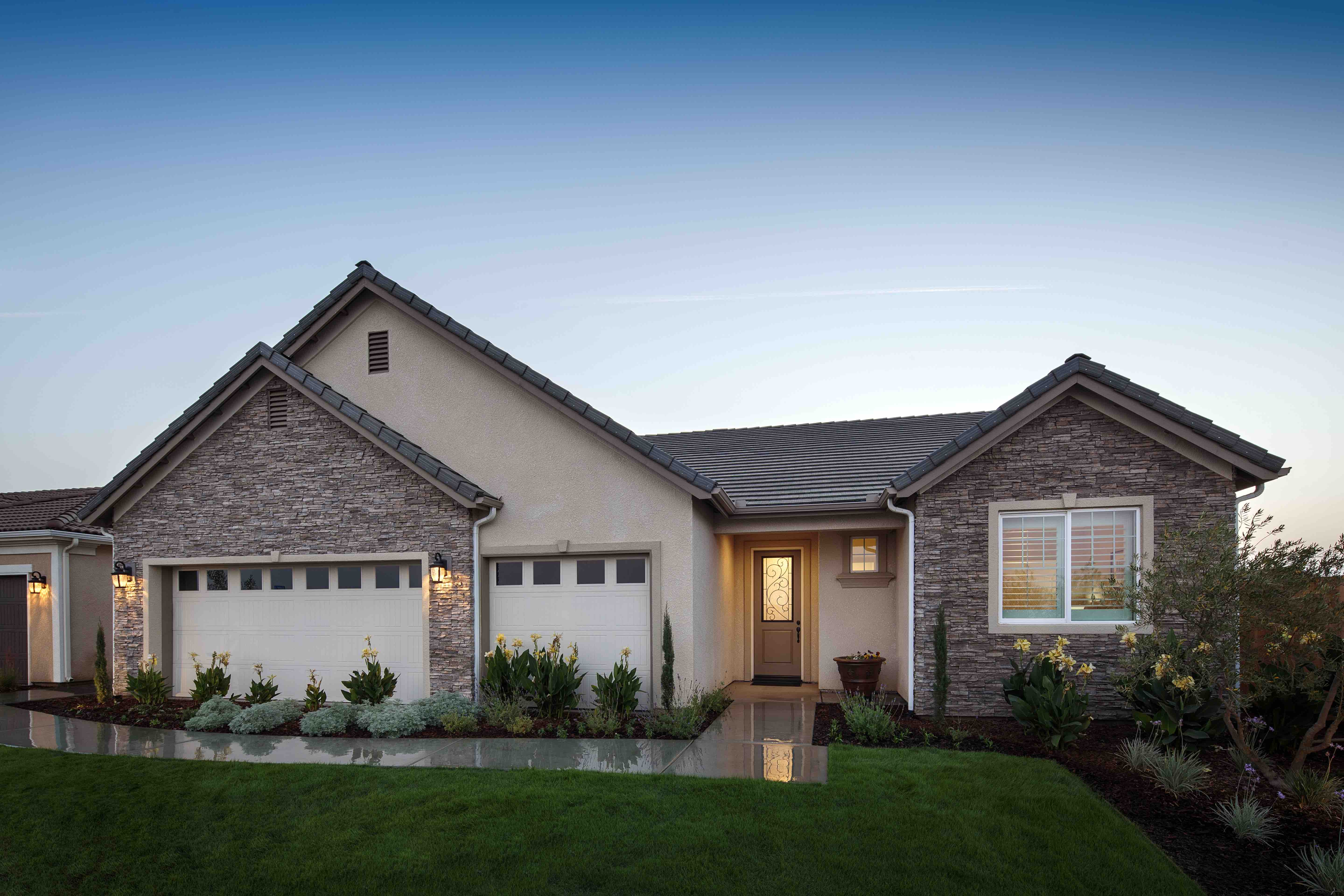 The Coronado plan with a French Country styled exterior at twilight